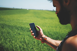 Mock up of bearded man looking in his smartphone in travel