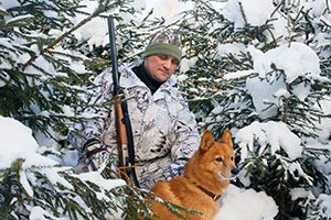 hunter with dog and gun on winter hunting
